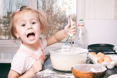 A little cute girl preparing the dough in the kitchen at home stock images