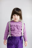 Little cute girl in purple clothes on grey background Stock Image