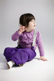 Little cute girl in purple clothes trying to hear  on grey backg Royalty Free Stock Image