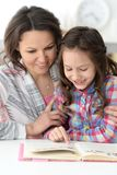 Little cute girl reading book with mother stock images