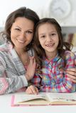 Little cute girl reading book with mother stock image