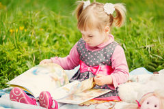 Little  cute girl reading a book in the warm sunny Royalty Free Stock Photos