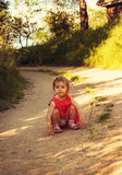Little cute girl in red dress is sitting on the road Stock Images