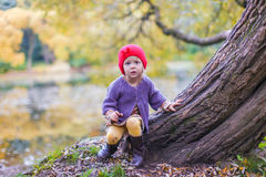 Little cute girl in red hat having fun at autumn Royalty Free Stock Photo