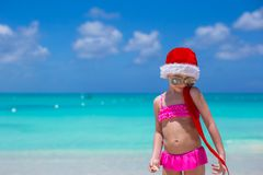 Little cute girl in red hat santa claus on the. Little girl in red hat santa claus on the beach Stock Images
