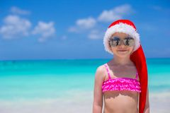 Little cute girl in red hat santa claus on the. Little girl in red hat santa claus on the beach Stock Image