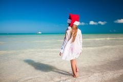 Little cute girl in red hat santa claus on the. Beach. This image has attached release Royalty Free Stock Images