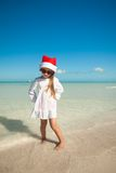Little cute girl in red hat santa claus and. Sunglasses on the beach. This image has attached release Stock Photos