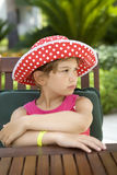 Little cute girl in red Panama sitting at table Stock Image