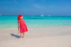 Little cute girl in red Santa hat on the beach. Little cute girl in red hat santa claus on the beach Stock Image