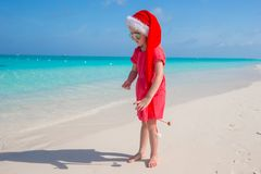 Little cute girl in red Santa hat on the beach Stock Image