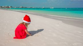 Little cute girl in red Santa hat playing on the Stock Image