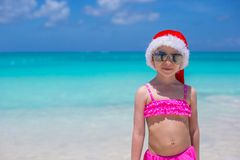 Little cute girl in red Santa hat on tropical Royalty Free Stock Photography