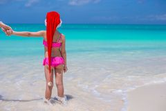 Little cute girl in red Santa hat on tropical Stock Images