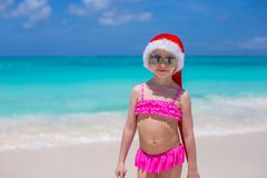 Little cute girl in red Santa hat on tropical Royalty Free Stock Photos