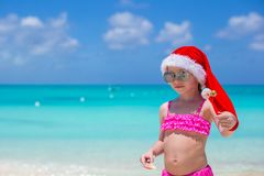 Little cute girl in red Santa hat on tropical Royalty Free Stock Image
