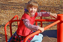 Little cute girl in red vest sits and rides on carousel Royalty Free Stock Images