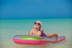 Little cute girl relax on pink air-bed in warm sea Stock Image