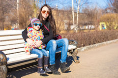Little cute girl relax with young mother at sunny day in the city Royalty Free Stock Photos
