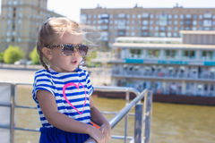 Little cute girl relaxing on a luxury ship sailing in the big city Stock Image