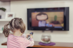 Little cute girl with remote changes channel on tv Royalty Free Stock Photography