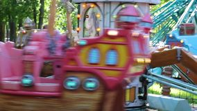 Little cute girl ride on carousel as pirate ships stock video