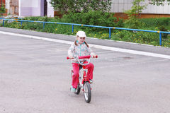 Little cute girl rides bicycle on parking Royalty Free Stock Photo