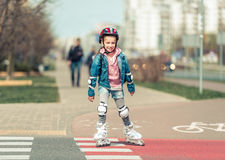 Little cute girl riding on roller skates Stock Photo
