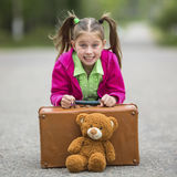 Little cute girl on the road with a suitcase Stock Photo