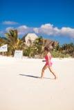Little cute girl running on the white sandy beach Stock Photos