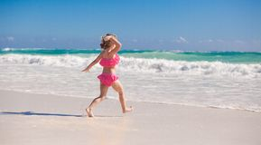 Little cute girl running on the white sandy beach Royalty Free Stock Image