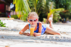Little cute girl on the sand at the beach in sun glasses with a glass of exotic cocktail juice Stock Image