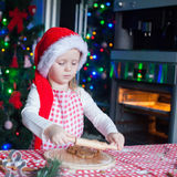 Little cute girl in Santa hat bake gingerbread Stock Images