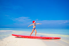 Little cute girl in Santa hat during beach Stock Images
