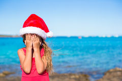 Little cute girl in santa hat covering her face Stock Photography