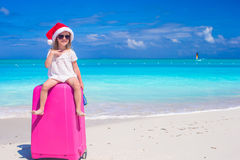 Little cute girl in Santa hat on suitcase at Stock Photo