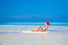 Little cute girl in Santa hat on white beach Royalty Free Stock Photos