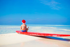 Little cute girl in Santa hat on white beach Royalty Free Stock Images