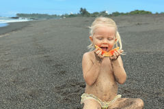 Little cute girl on the sea beach eating ripe papaya Royalty Free Stock Images