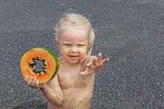Little cute girl on the sea beach with sweet orange papaya Stock Photography
