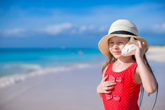 Little cute girl with seashell in hands at Stock Photo