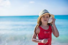 Little cute girl with seashell in hands at Stock Image