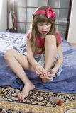 Little cute girl seven years old. Do pedicure sitting on sofa royalty free stock image