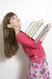 Little cute girl seven years old. Carry books. White background royalty free stock images