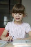 Little cute girl seven years old do homework. Stock Photos