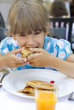 Little cute girl seven years old eat pancake. Have a breakfast. she hurry up royalty free stock photo