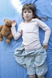 Little cute girl seven years old lying on bed. Little cute serious girl seven years old lying on bed stock images