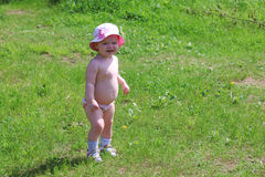 Little cute girl in shorts and panama stands on green grass Royalty Free Stock Image