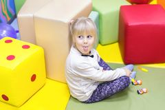 Little cute girl showing tongue while playing toys. Little cute  sly girl   showing tongue while playing toys at indoor playground Royalty Free Stock Image