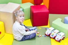 Little cute girl showing tongue while playing toys. Little cute  sly girl   showing tongue while playing toys at indoor playground Stock Photography